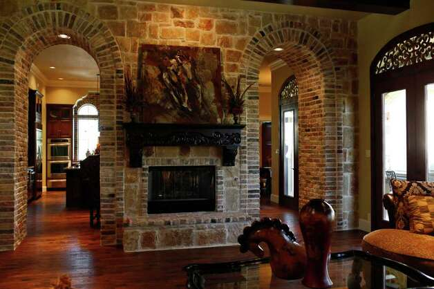 A stone fireplace is flanked by dual arched entryways in The Chateaux, by Garner Custom Home. Photo: LISA KRANTZ, SAN ANTONIO EXPRESS-NEWS / SAN ANTONIO EXPRESS-NEWS
