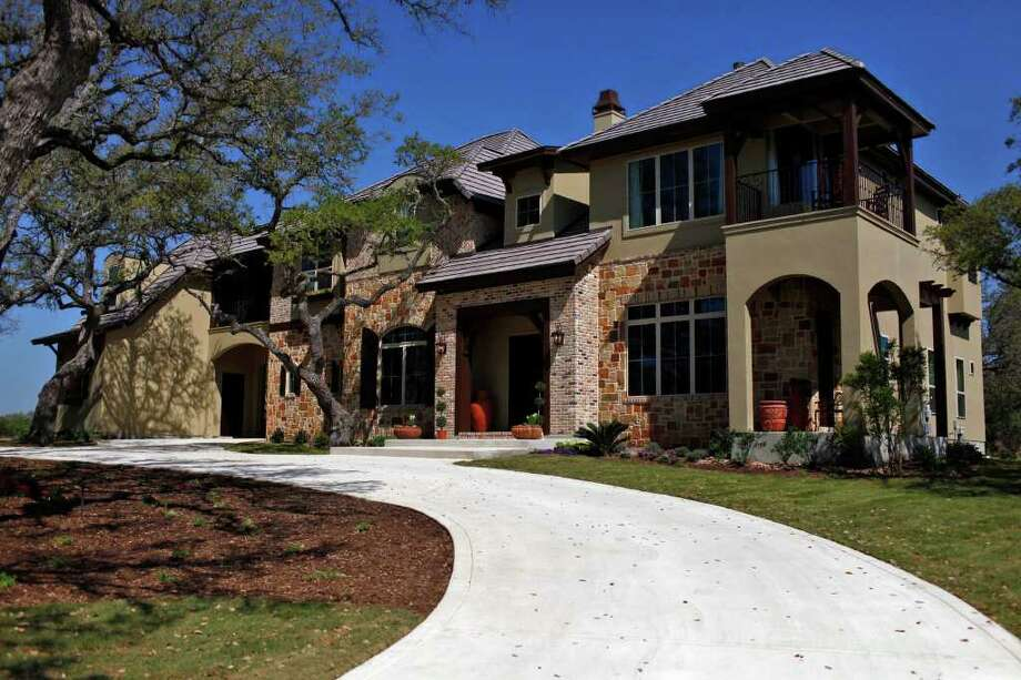 The Chateaux, a Garner Custom Home, features stone and brick accents, three outdoor living areas and an outdoor kitchen with a fireplace. Photo: LISA KRANTZ, SAN ANTONIO EXPRESS-NEWS / SAN ANTONIO EXPRESS-NEWS