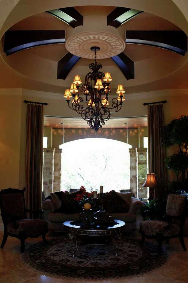 A grand chandelier hangs above a sitting area in the Trinity at Stone Creek home. Photo: LISA KRANTZ, SAN ANTONIO EXPRESS-NEWS / SAN ANTONIO EXPRESS-NEWS