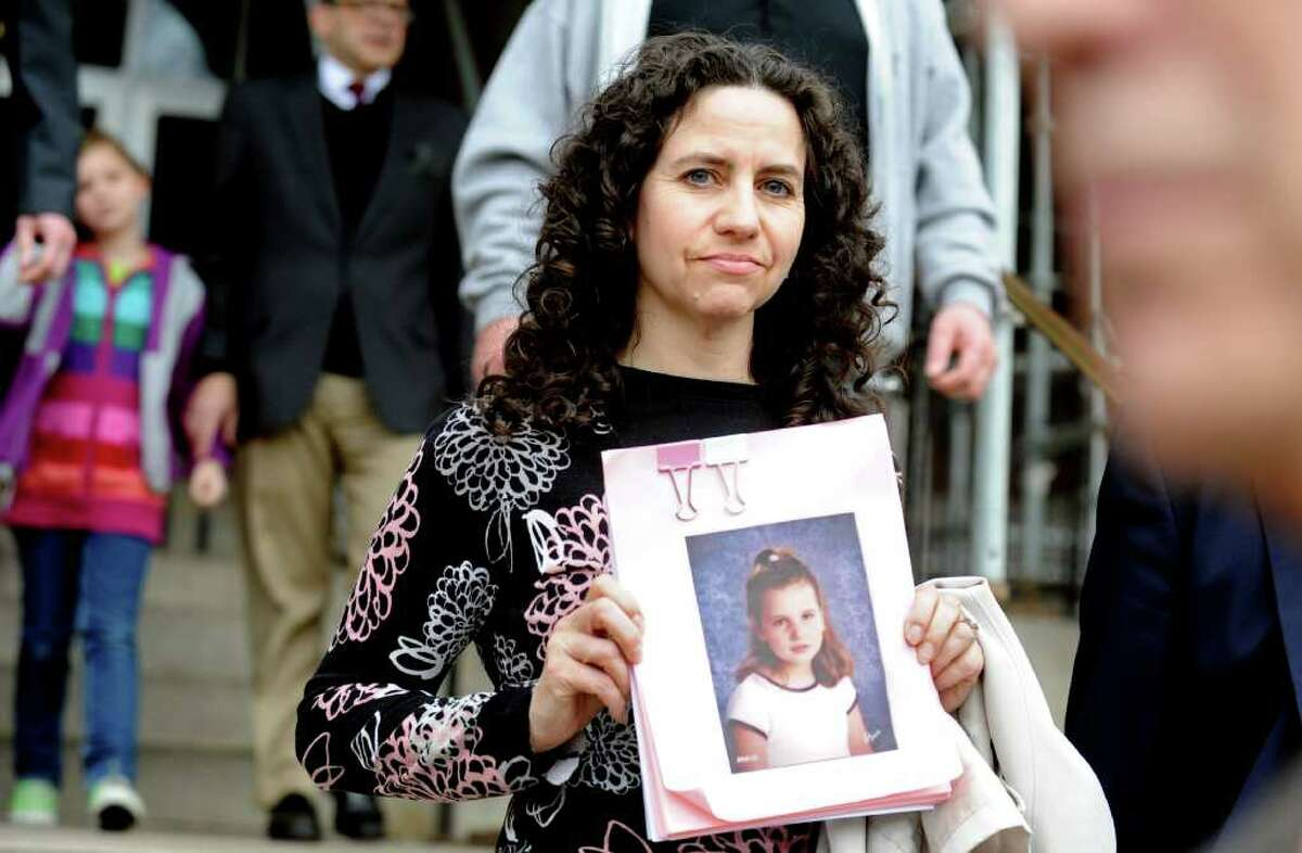 Kim Stagliano holds a photo of her daughter Isabella as she leaves Superior Court in Bridgeport, Conn. Friday, April 8, 2011 following a hearing for former Trumbull school bus driver Evelyn Guzman. Guzman was accused of sending and receiving a total of 1,068 text messages while transporting special needs children, including Isabella. In addition, Guzman's daughter Jennifer Davila, who was working as a bus monitor on Guzman's bus, was arrested in August for allegedly assaulting 9-year-old Isabella while she was riding on the bus.