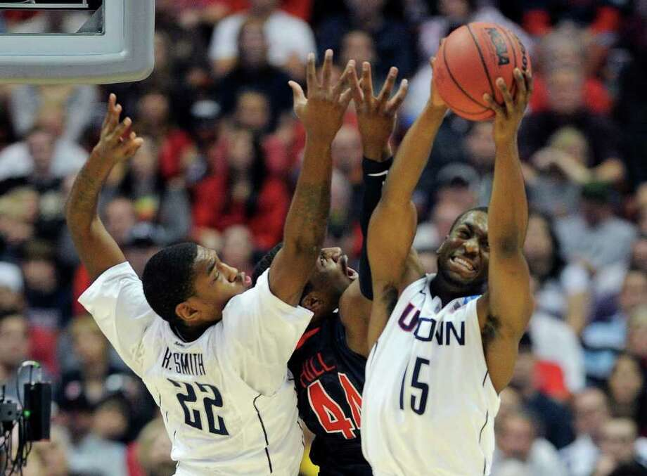 Connecticut's Roscoe Smith, left, goes and Kemba Walker, right, battle for a rebound with Arizona's Solomon Hill, center, during the first half of a West regional final in the NCAA college basketball tournament, Saturday, March 26, 2011, in Anaheim, Calif.  (AP Photo/Mark J. Terrill) Photo: Mark J. Terrill, ST / AP