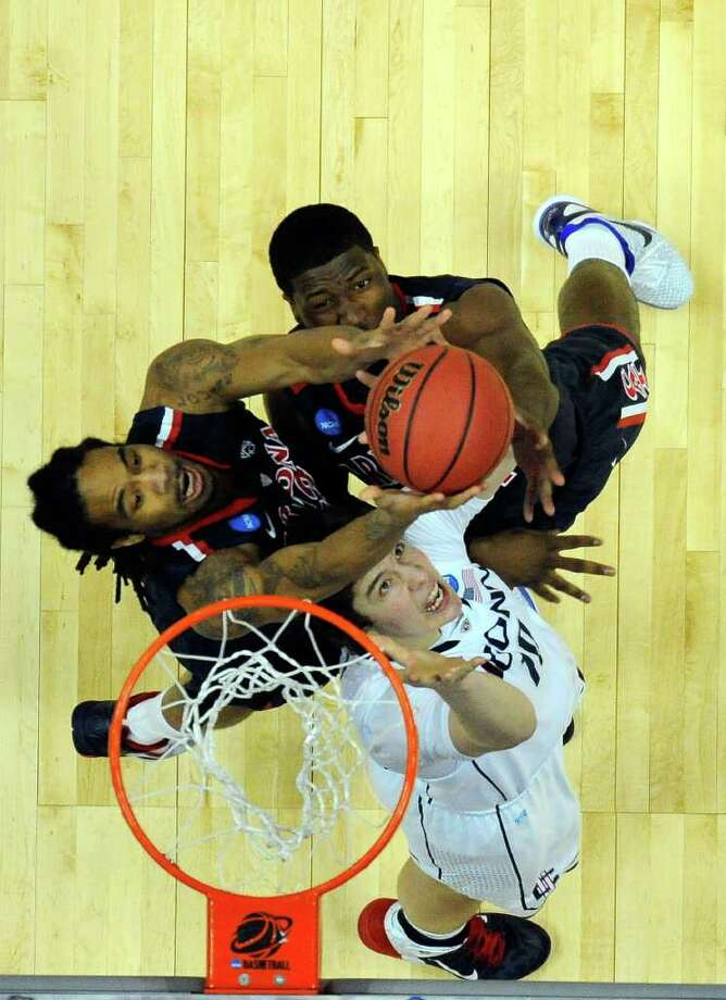 ANAHEIM, CA - MARCH 26:  Jesse Perry #33 and Solomon Hill #44 of the Arizona Wildcats fight for a rebound against Tyler Olander #10 of the Connecticut Huskies during the west regional final of the 2011 NCAA men's basketball tournament at the Honda Center on March 26, 2011 in Anaheim, California.  (Photo by Kevork Djansezian/Getty Images) *** Local Caption *** Jesse Perry;Solomon Hill;Tyler Olander Photo: Kevork Djansezian, ST / 2011 Getty Images