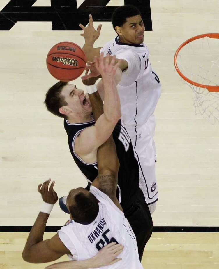 Butler's Andrew Smith, center, fights for a rebound against Connecticut's Jeremy Lamb, right, and Charles Okwandu during the first half of the men's NCAA Final Four college basketball championship game Monday, April 4, 2011, in Houston. (AP Photo/David J. Phillip) Photo: David J. Phillip, ST / AP2011