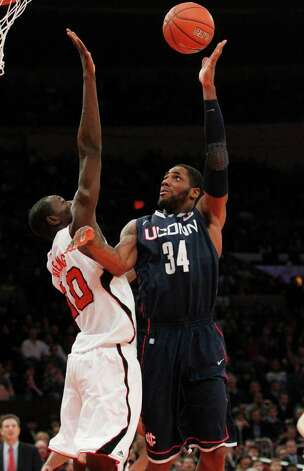 Connecticut's Alex Oriakhi (34) shoots over Louisville's Gorgui Dieng (10) during the first half of an NCAA college basketball game at the Big East Championship ,Saturday, March 12, 2011, in New York. (AP Photo/Frank Franklin II) Photo: Frank Franklin II, ST / AP