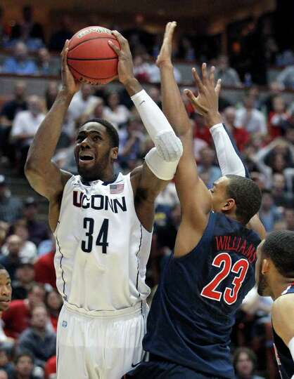 Arizona's Derrick Williams attempts to block the shot of Connecticut's Alex Oriakhi during the secon