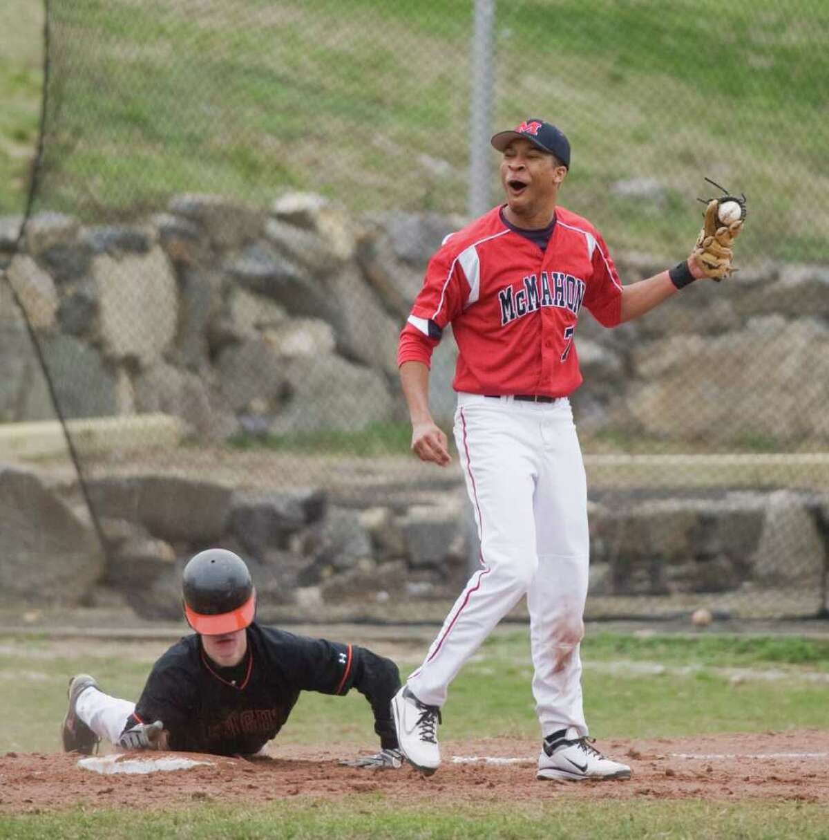 McMahon's Ronnie Sherman reacts to the call as Stamford High's Jeff Cooper beats the tag at third in baseball action at Stamford, Conn. on Friday April 8, 2011.