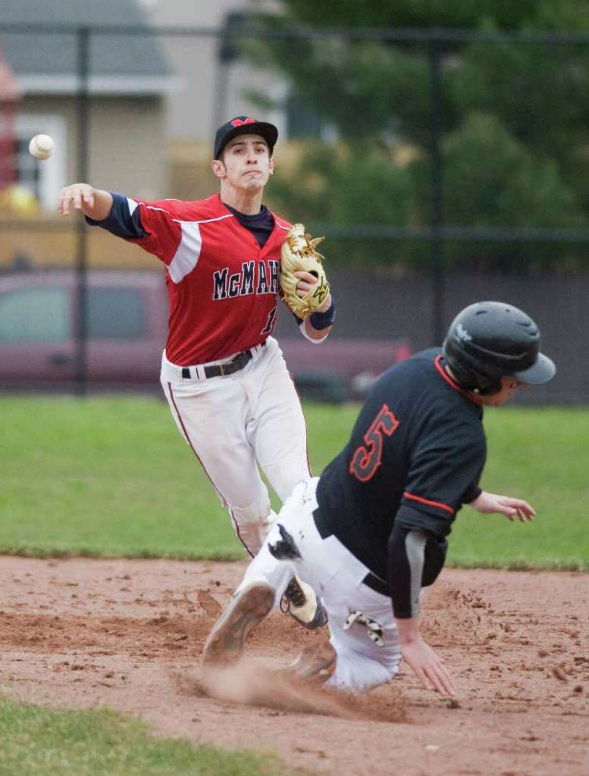 McMahon High School's Bryan Daniello makes the throw to first as Stamford High's Tommy Fabricatore arrives late in baseball action at Stamford, Conn. on Friday April 8, 2011.