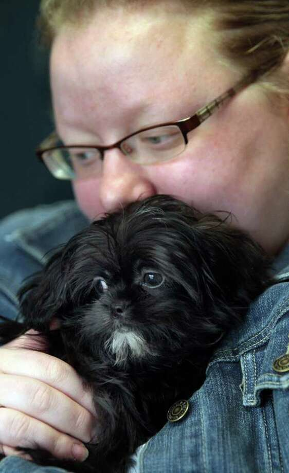 Johanna Krumer of Latonia, Ky. holds her dog Spike during a Pets in Need event at the Kenton County Animal Shelter in Covington, Ky. on Saturday, April 2, 2011 where dog owner residents could have their pets attended to by a veterinarian for a discounted price. Photo: AP Photo/The Cincinnati Enquirer,  Ernest Coleman