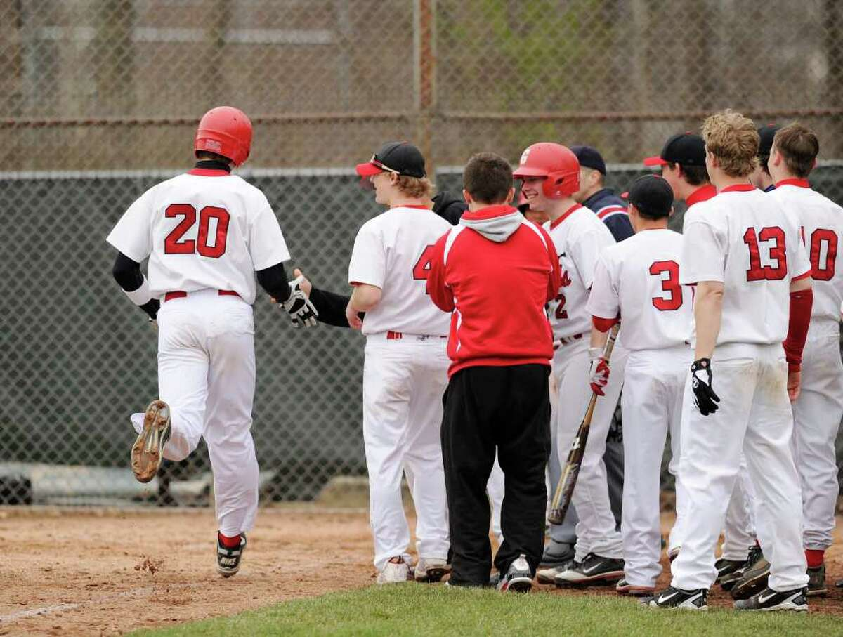 Taylor Olmstead, left, # 20 of Greenwich High School, is congratulated by his teammates after hitting a 2-run homer during baseball game between Greenwich High School and Ridgefield High School at Greenwich High School, Friday afternoon, April 8, 2011. GHS lost the game 4-2.