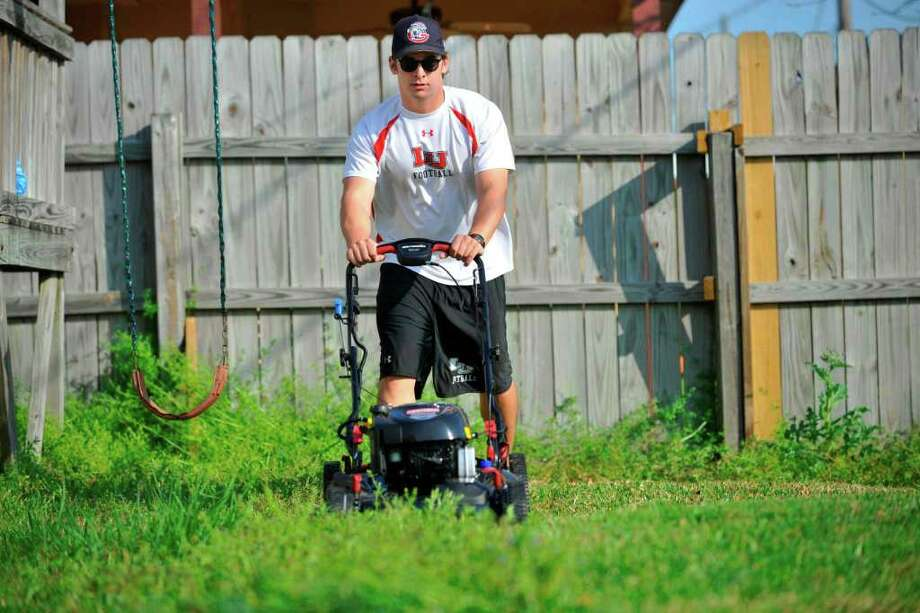 """Lamar football player Harrison Tatum works on mowing a lawn for a Groves client on Wednesday afternoon.  The Cardinal entrepreneur supplements his football scholarship with his lawn-mowing business called """"Lawn Barbers.""""   March 23, 2011.  Valentino Mauricio/The Enterprise Photo: Valentino Mauricio / Beaumont"""