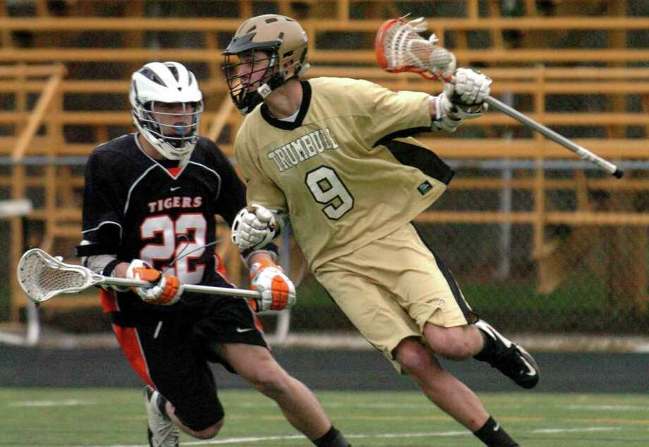 Trumbull's #9 Matt Gasper works to get past Ridgefield's #22 Will Bonaparte behind the goal, during boys lacrosse action in Trumbull, Conn. on Friday April 8, 2011. Photo: Christian Abraham / Connecticut Post