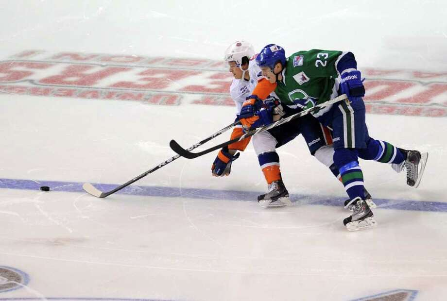 Bridgeport's Rhett Rakhshani, left, and Hartford's Dale Weise, right, compete for control of the puck during Friday's game against Hartford at Webster Bank Arena at Harbor Yard on April 8, 2011. Photo: Lindsay Niegelberg / Connecticut Post