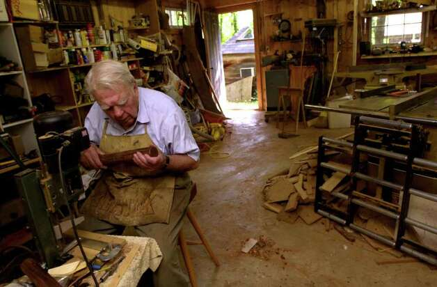 Andy Rooney examines a table leg as he works on in his woodshop in August 2001 at his home in Rensselaerville, N.Y. (Cindy Schultz/Times Union archive) Photo: CINDY SCHULTZ / ALBANY TIMES UNION