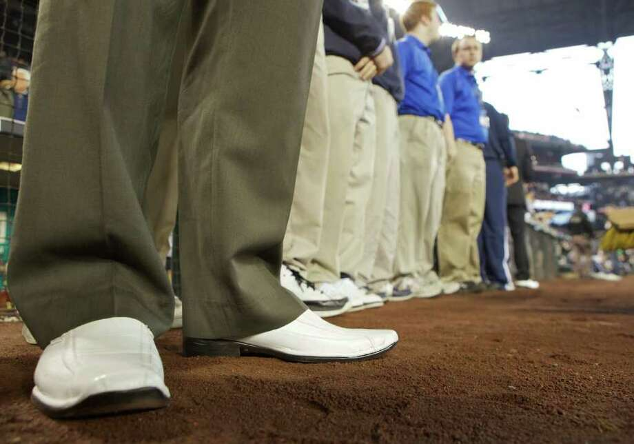 A Mariners employee dons white shoes in memory of former Mariners announcer Dave Niehaus during Opening Day ceremonies at Safeco Field in Seattle Friday April 8, 2011. Photo: Stephen Brashear