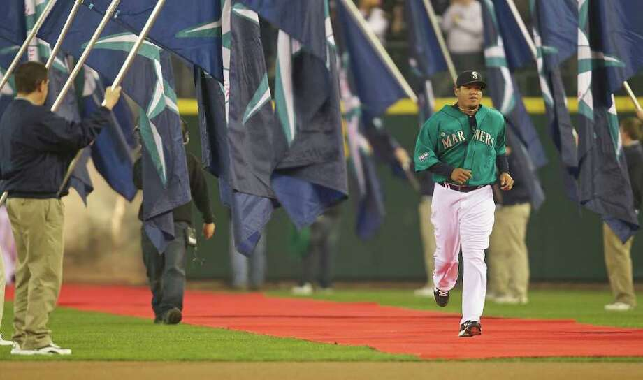 Seattle Mariners Cy Young Award-winning pitcher Felix Hernandez runs on to the field during Opening Day ceremonies at Safeco Field in Seattle Friday April 8, 2011. Photo: Stephen Brashear