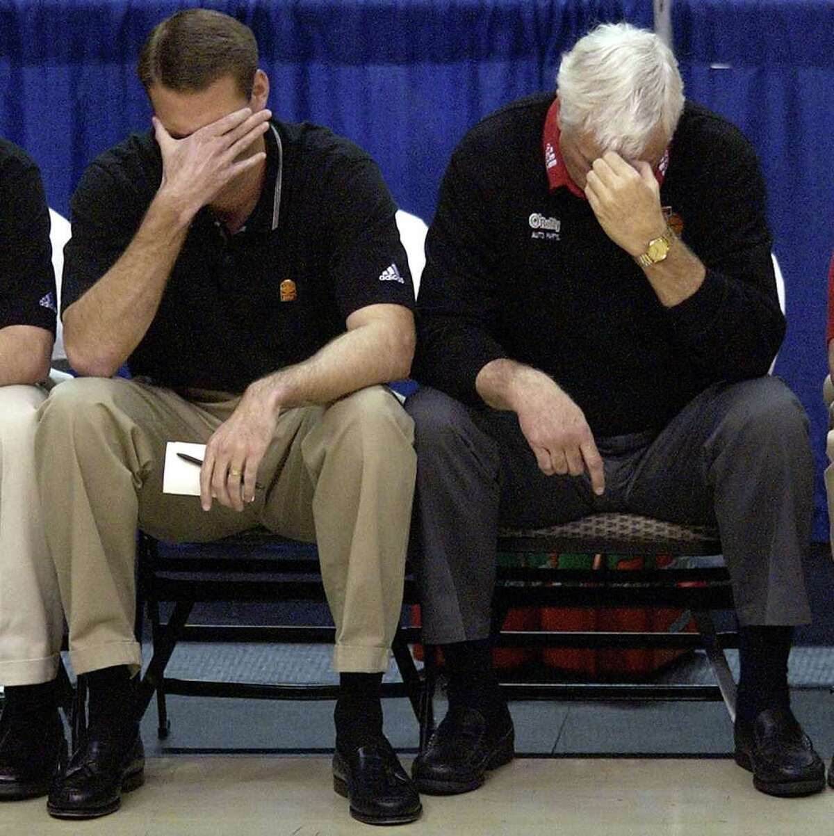 Texas Tech head coach Bobby Knight, right, and assistant coach Pat Knight, left, cover their faces late in the 82-77 loss to Oklahoma State, Saturday, March 13, 2004, during the semi finals of the Big 12 Tournament in Dallas. (AP Photo/Tony Gutierrez)