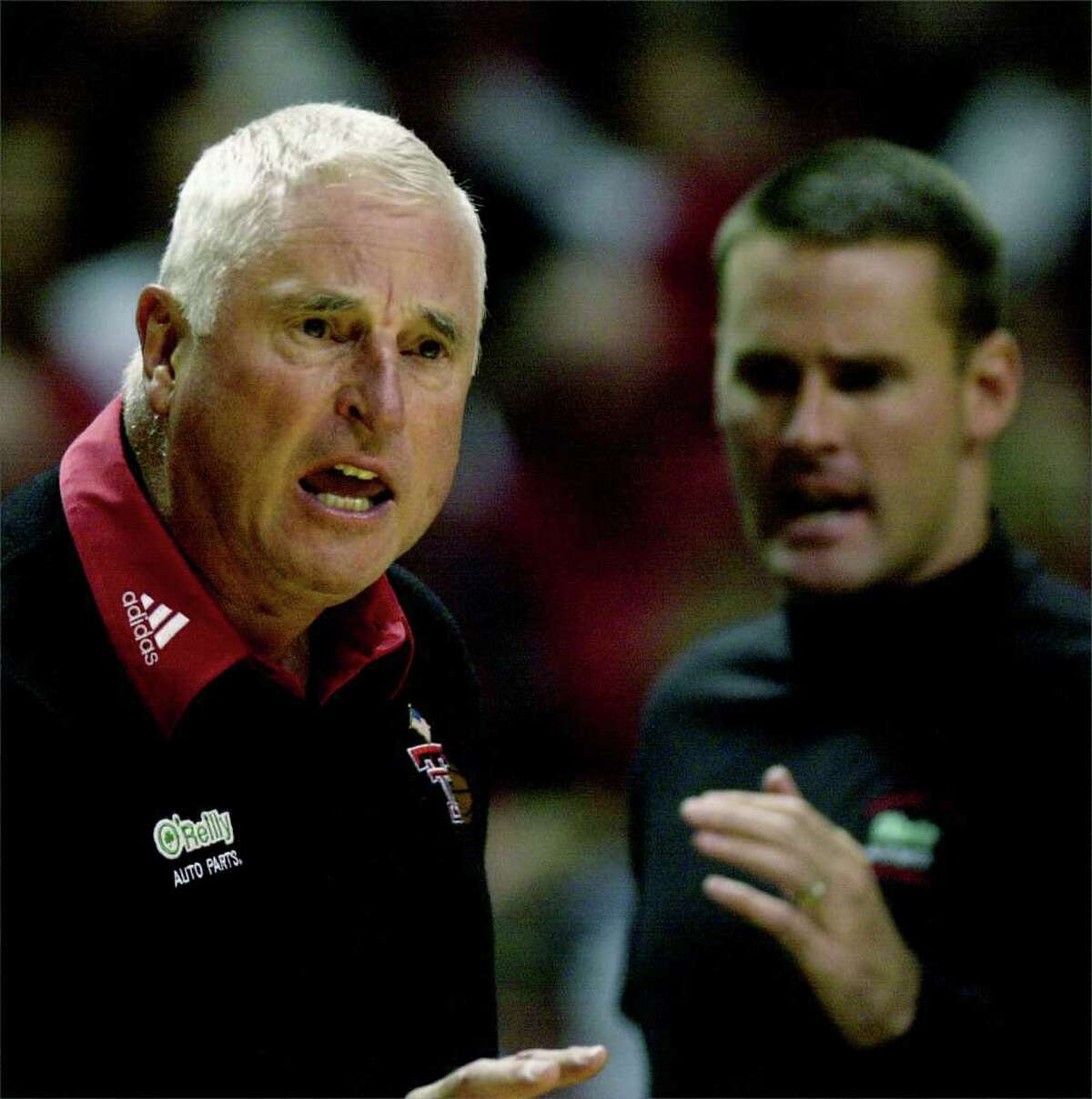 Texas Tech coach Bob Knight disputes a charging call during the first half against Centenary, Saturday night, Nov. 27, 2004, in Lubbock, Texas. At right is Knight's son and associate coach Pat Knight. (AP Photo/Lubbock Avalanche-Journal, Joe Don Buckner)