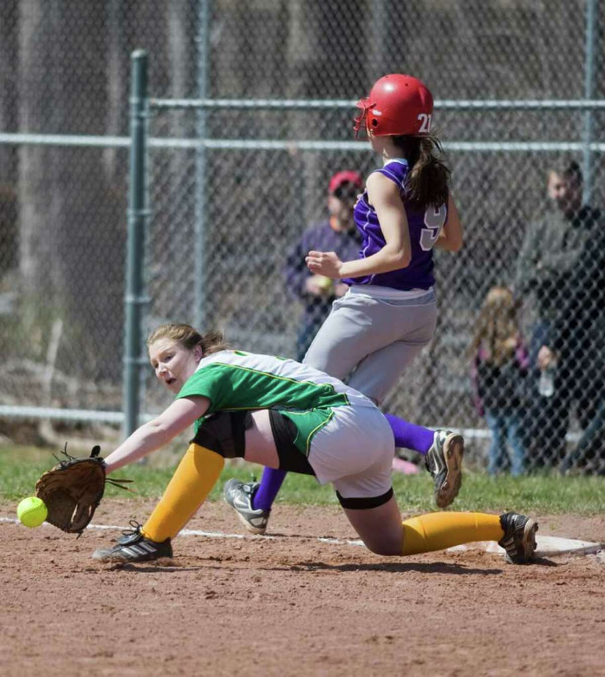 Trinity Catholic's Katelyn Spielman reaches for the throw as Westhill's Megan DelAssandro arrives safely at first in softball action in Stamford, Conn. on Saturday April 9, 2011.