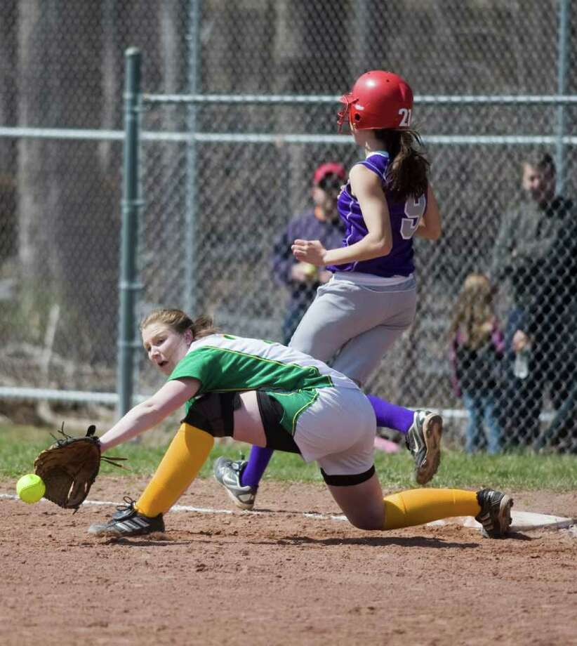 Trinity Catholic's Katelyn Spielman reaches for the throw as Westhill's Megan DelAssandro arrives safely at first in softball action in Stamford, Conn. on Saturday April 9, 2011. Photo: Kathleen O'Rourke / Stamford Advocate