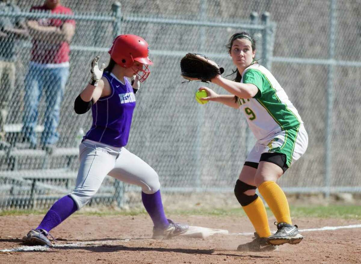 Westhill High's Cassandra Kish stays on third as Trinity Catholic's Kelly Sheridan looks to make the throw to first in softball action in Stamford, Conn. on Saturday April 9, 2011.