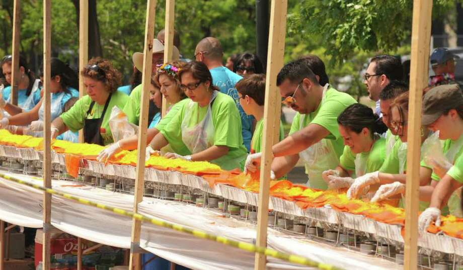 April 2011: More than 200 volunteers helped construct a 300-foot, 1.5-ton enchilada in Milam Park. The attempt didn't set a Guinness World Record, because the enchilada wasn't made with one giant tortilla. Photo: Robin Jerstad/Special To The Express-News / Robert Jerstad