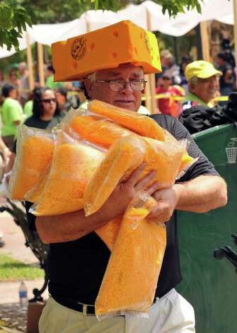 Dave Moore carries some of the 1,500 pounds of Wisconsin Mild Cheddar cheese that was used to construct a 300-foot-long enchilada in Milam Park on April 9, 2011. Photo: Robin Jerstad/Special To The Express-News / Robert Jerstad