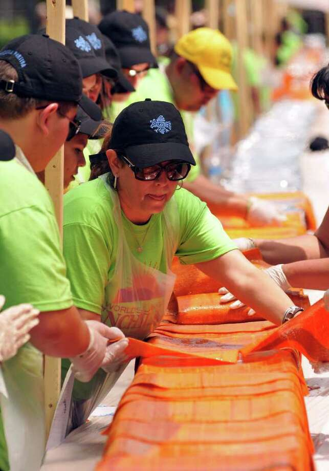 Susie Mitchel layers tortillas during the construction of a 300-foot-long enchilada in Milam Park on April 9, 2011. The project was a collaboration of 20 San Antonio restaurants and the Rey Feo Consejo Foundation. Photo: Robin Jerstad/Special To The Express-News / Robin Jerstad