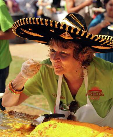 Debbie Gonzalez has a bite of the 300-foot-long enchilada created in Milam Park on April 9, 2011, by 20 San Antonio restaurants and the Rey Feo Consejo Foundation. Photo: Robin Jerstad/Special To The Express-News / Copyright 2011 by Robin Jerstad, Jerstad Photographics LLC, 210-254-6552