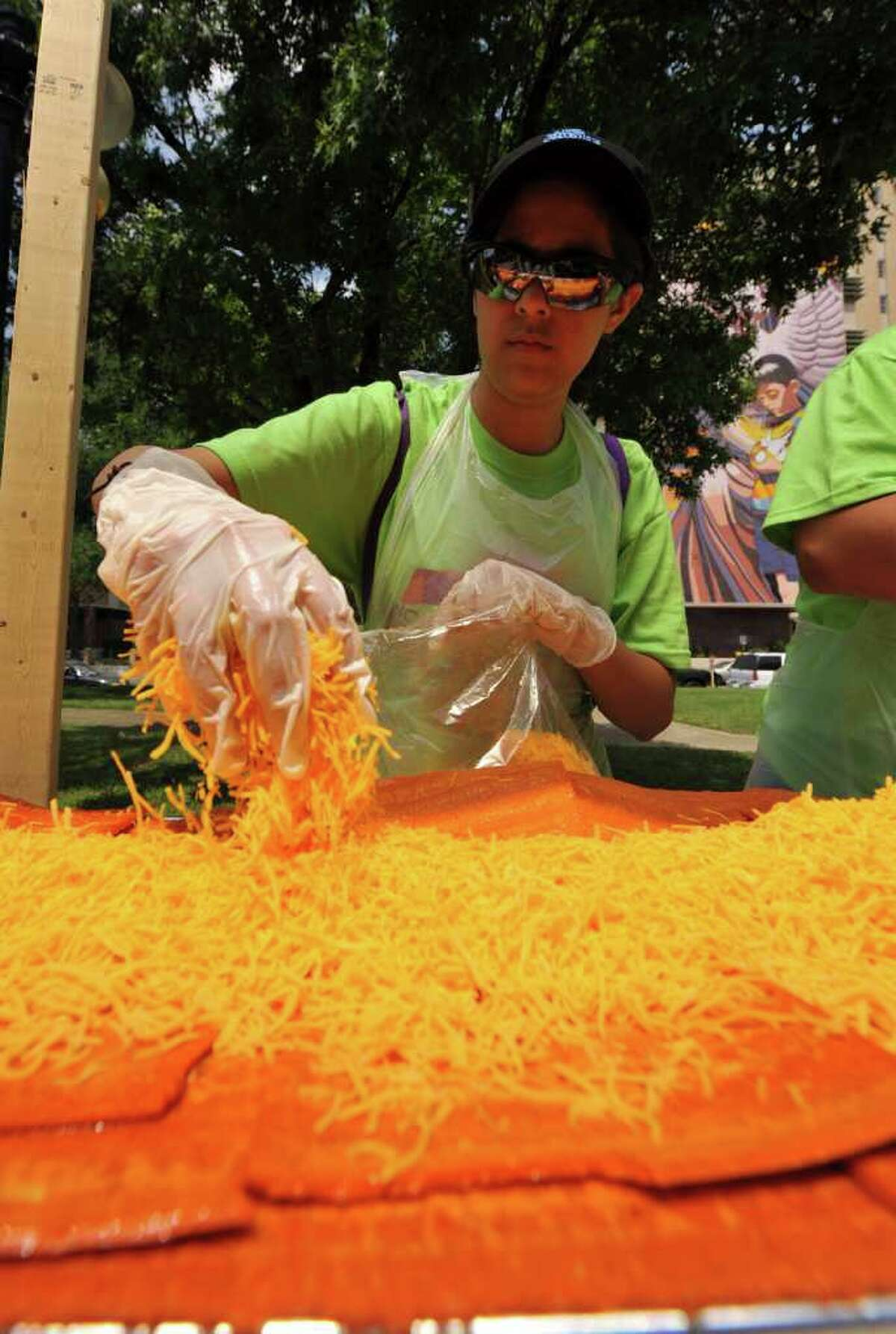 Susie Mitchell layers on some of the 1,500 pounds of Wisconsin Mild Cheddar cheese that made up the 300-foot-long enchilada made in Milam Park on April 9, 2011, as part of a collaboration between 20 local restaurants and the Rey Feo Consejo Foundation.