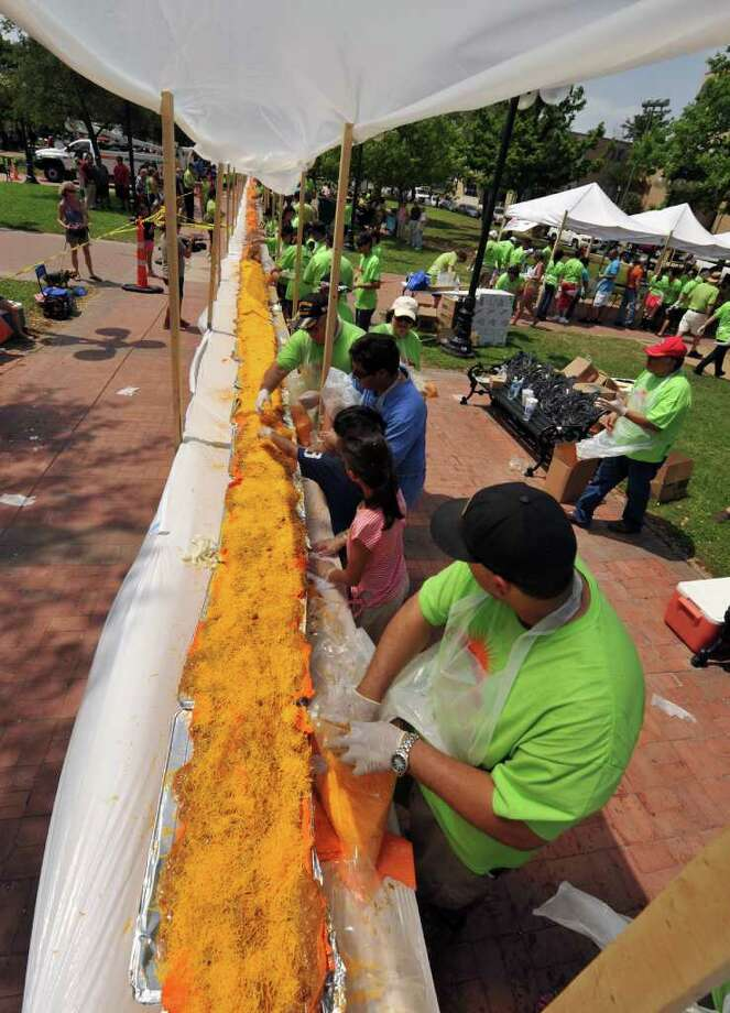 Anyone's abuelita can make a cheese enchilada, but it took the collaboration of 20 local restaurants, 200 volunteers and 1,900 pounds of cheddar cheese to make a 1.5-ton, 300 foot-long cheese enchilada in Milam Park in San Antonio, Texas, on April 9, 2011, according to Nick Garza, the event's organizer. Photo: Robin Jerstad/Special To The Express-News / Copyright 2011 by Robin Jerstad, Jerstad Photographics LLC, 210-254-6552