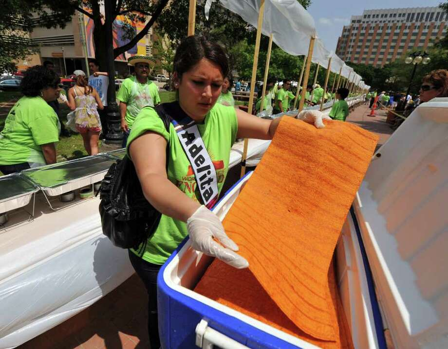 Adrienne Borrego-Horn begins the process of distributing tortillas for the 300-foot-long enchilada that was created in Milam Park on April 9, 2011. The enchilada used 1,500 pounds of cheese. Photo: Robin Jerstad/Special To The Express-News / Copyright 2011 by Robin Jerstad, Jerstad Photographics LLC, 210-254-6552