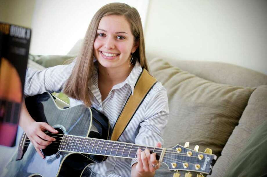 Lorena Sferlazza, 17 is a senior at Norwalk High School is this years recipient of the $100,000 Kevin M. Eidt Memorial Scholarship.  She plays guitar and piano and is leaning towards Holy Cross as her college choice. She sits in her home in Norwalk, Conn. on Saturday April 9, 2011. Photo: Kathleen O'Rourke / Stamford Advocate