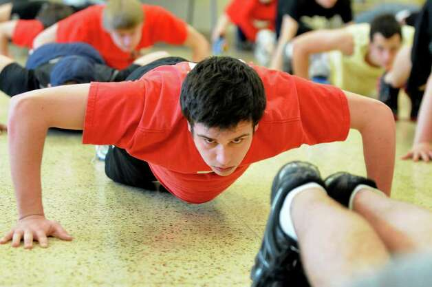 Tommy Vitale, 16, holds a push up during strength training with the rowing team on Wednesday, April 6, 2011, at Niskayuna High. Budget cuts have trimmed the offerings at many high schools.  (Cindy Schultz / Times Union) Photo: Cindy Schultz