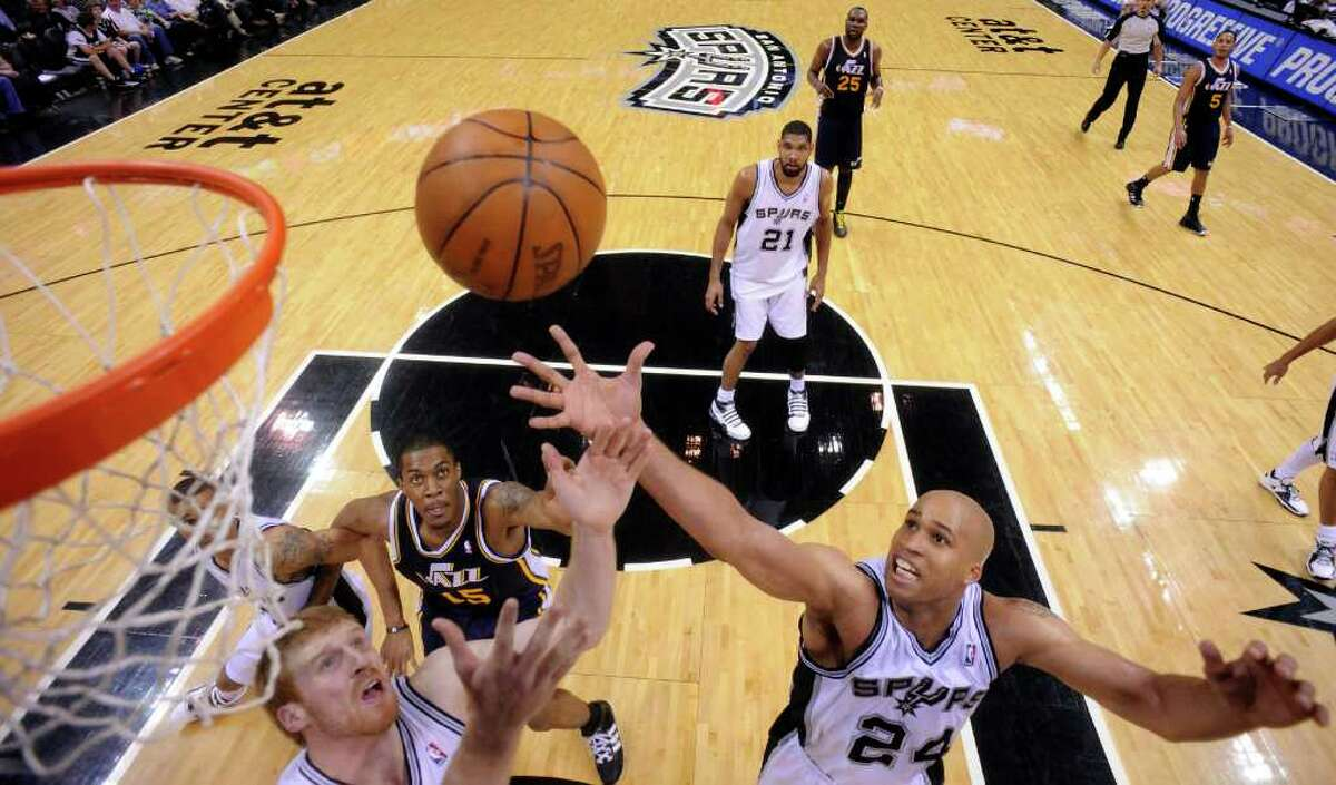 Spurs' Matt Bonner and Spurs' Richard Jefferson grab for a rebound against Jazz's Derrick Favors during second half action Saturday April 9, 2011 at the AT&T Center. The Spurs won 111-102. (PHOTO BY EDWARD A. ORNELAS/eaornelas@express-news.net)