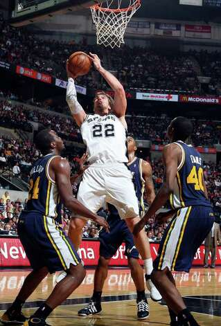Spurs' Tiago Splitter shoots between Jazz defenders during second half action Saturday April 9, 2011 at the AT&T Center. The Spurs won 111-102.  (PHOTO BY EDWARD A. ORNELAS/eaornelas@express-news.net) / SAN ANTONIO EXPRESS-NEWS (NFS)