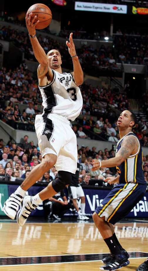 Spurs' George Hill shoots around  Jazz's Devin Harris during second half action Saturday April 9, 2011 at the AT&T Center. The Spurs won 111-102.  (PHOTO BY EDWARD A. ORNELAS/eaornelas@express-news.net) / SAN ANTONIO EXPRESS-NEWS (NFS)