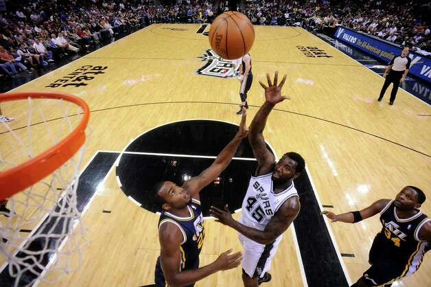 Spurs' DeJuan Blair shoots between Jazz's Paul Millsap (left) and Jazz's C.J. Miles during first half action Saturday April 9, 2011 at the AT&T Center.  (PHOTO BY EDWARD A. ORNELAS/eaornelas@express-news.net) / SAN ANTONIO EXPRESS-NEWS (NFS)