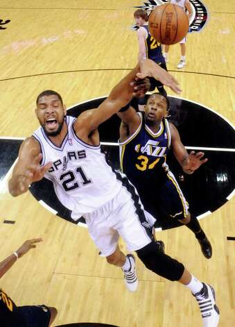 Spurs' Tim Duncan is defended by Jazz's C.J.  Miles during first half action Saturday April 9, 2011 at the AT&T Center.  (PHOTO BY EDWARD A. ORNELAS/eaornelas@express-news.net) / SAN ANTONIO EXPRESS-NEWS (NFS)