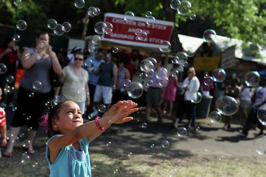 Eriah (ck) Bachman, 5, plays with bubbles being sprayed from one of the booths at Taste of New Orleans at Sunken Gardens Saturday, April 9, 2011. Photo: Jennifer Whitney, Jennifer Whitney/Special To The San Antonio Express-News / special to the Express-News