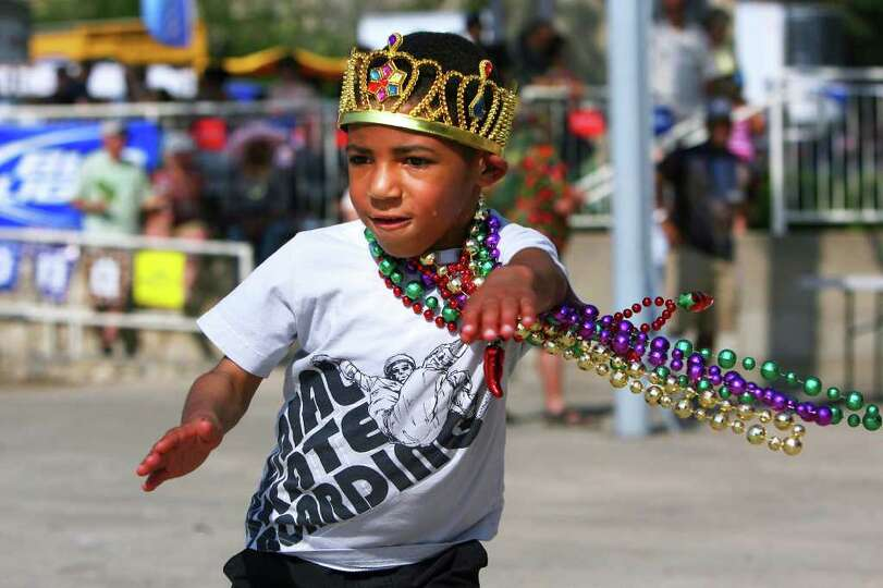 Robert Bore, 5, adorned in Mardi Gras gear, dances to the music during Taste of New Orleans at Sunke