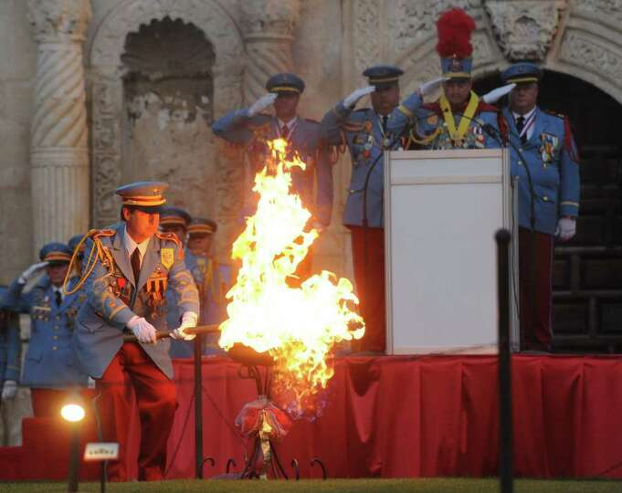 The outgoing King Antonio, Nick Campbell, lights a flame in Alamo Plaza as the new King Antonio, Bil