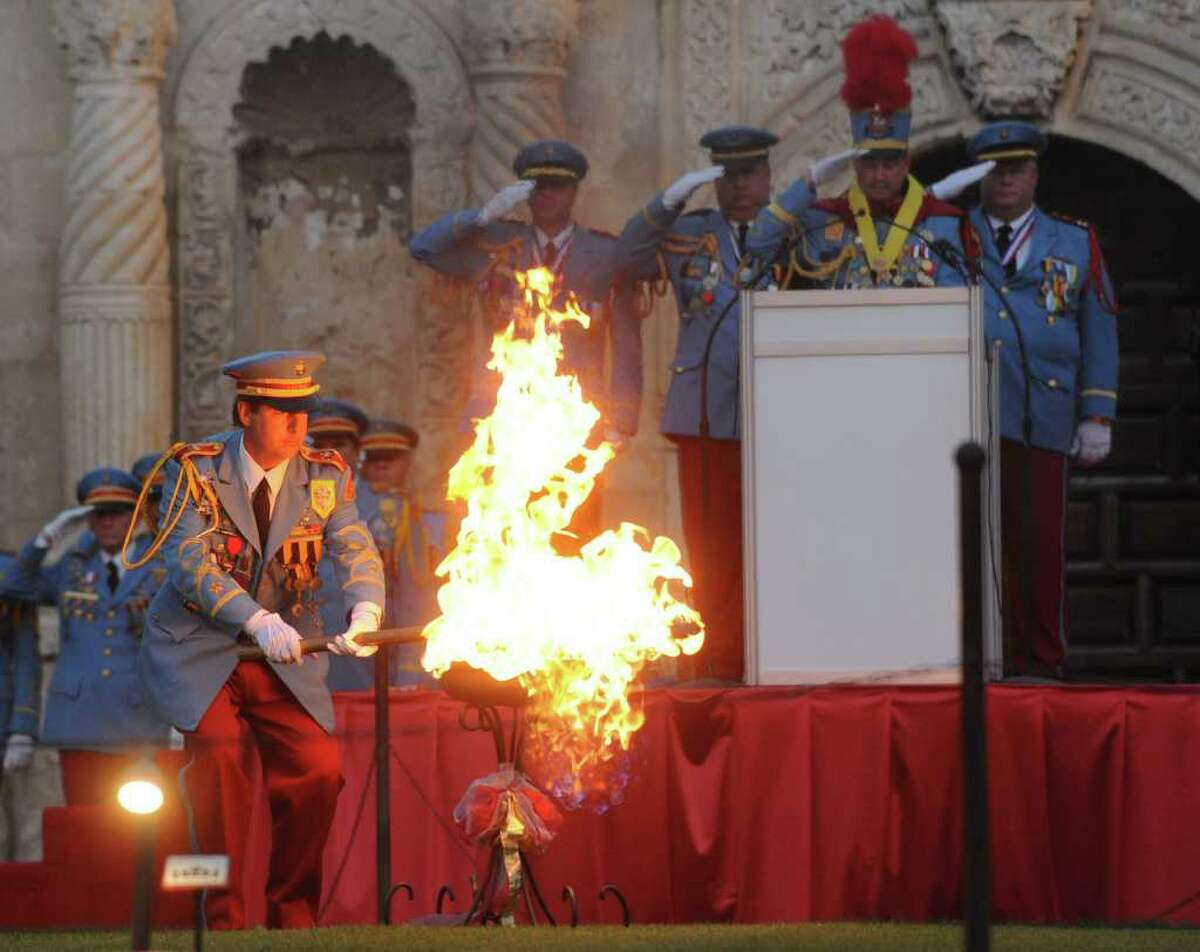 The outgoing King Antonio, Nick Campbell, lights a flame in Alamo Plaza as the new King Antonio, Bill Mitchell, stands at the podium during a ceremony on Saturday evening. April 9, 2011. King Antonio, one of the longest-standing Fiesta traditions, is a member of the royalty who reign over the merriment of Fiesta. BILLY CALZADA / gcalzada@express-news.net