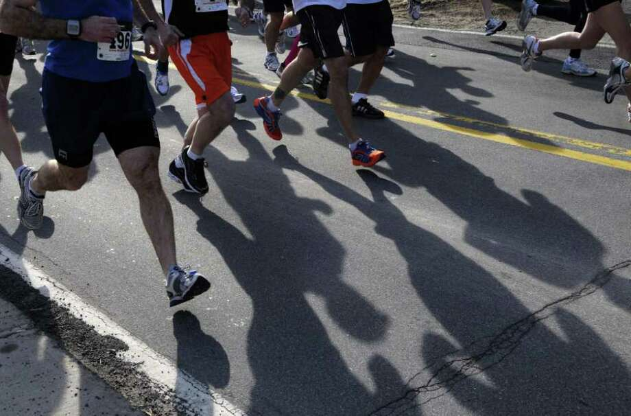 Runners cast their shadows on the street during the annual Delmar Dash on Sunday morning, April 10, 2011 in Delmar, NY.  This is the twenty third year for the event billed as a family fitness 5 mile run geared towards adults and kids.  (Paul Buckowski / Times Union) Photo: Paul Buckowski / 00012685A