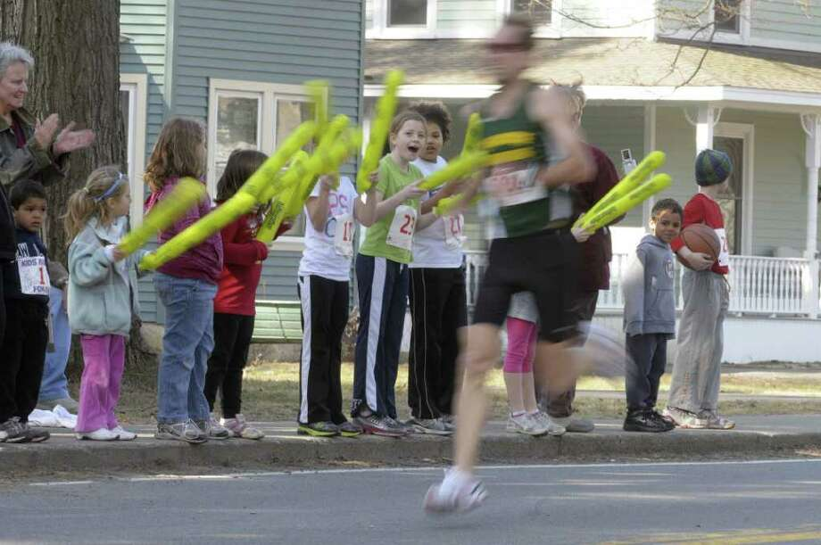 A group of children cheer on adult runners during the annual Delmar Dash on Sunday morning, April 10, 2011 in Delmar, NY.  This is the twenty third year for the event billed as a family fitness 5 mile run geared towards adults and kids.  (Paul Buckowski / Times Union) Photo: Paul Buckowski / 00012685A