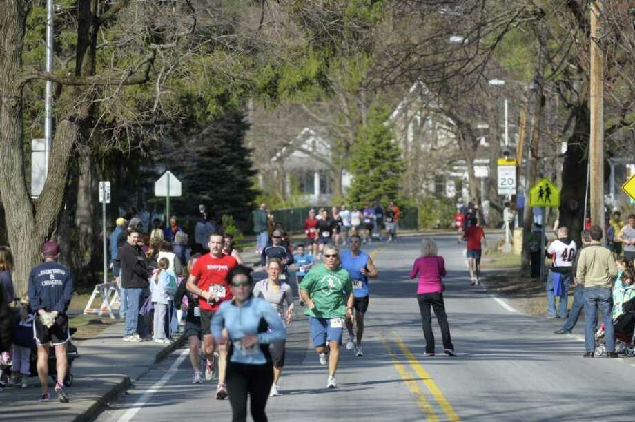 Runners head down Kenwood Avenue as they head towards the finish line during the annual Delmar Dash on Sunday morning, April 10, 2011 in Delmar, NY.  This is the twenty third year for the event billed as a family fitness 5 mile run geared towards adults and kids.  (Paul Buckowski / Times Union) Photo: Paul Buckowski / 00012685A