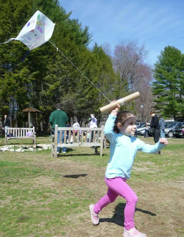 Sabrina Crespi, 5, of Weston, runs to coax her homemade kite aloft Saturday at Earthplace in Westport. Photo: Contributed Photo/Mike Lauterborn / Westport News contributed