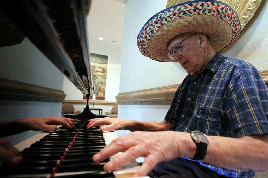 John Mcauliffe, 97, plays old classics from memory on the piano near the dining room at The Inn at Los Patios where he lives, Sunday, April 10, 2011.  During Fiesta he wears a sombrero given to him by his grandson. Photo: Jennifer Whitney, Jennifer Whitney/Special To The San Antonio Express-News / special to the Express-News