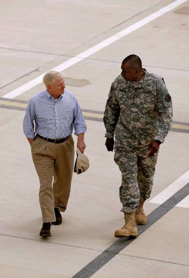 Defense Secretary Robert Gates walks with Gen. Lloyd Austin, commanding general of U.S. forces in Iraq, across the tarmac while switching airplanes in Irbil, Iraq, Friday, April 8, 2011.  (AP Photo/Chip Somodevilla, Pool) Photo: Chip Somodevilla