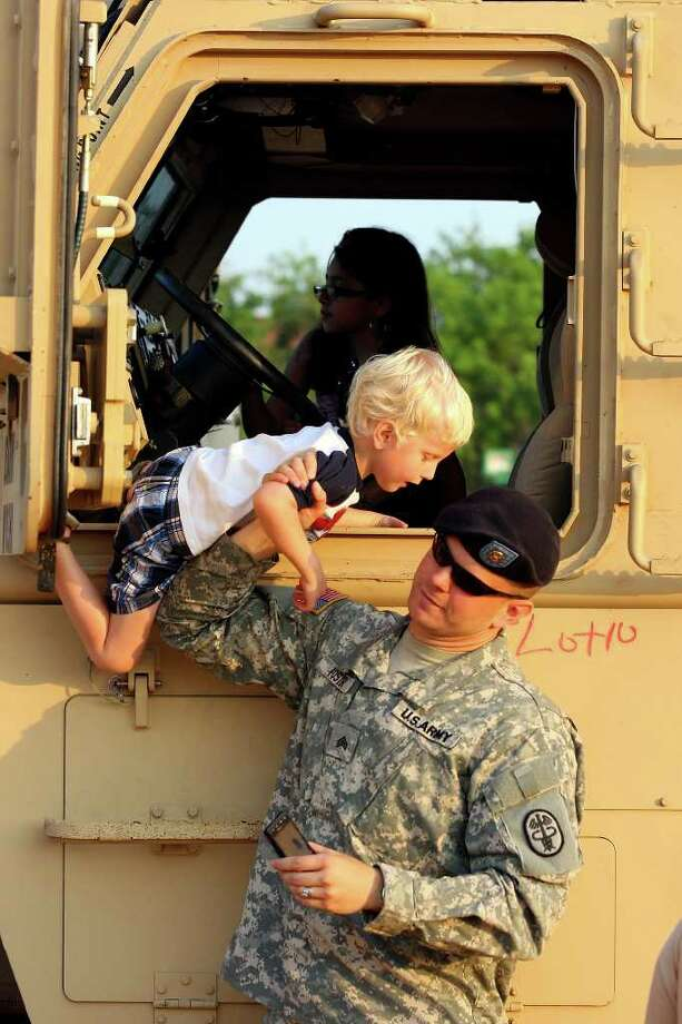 FOR METRO - U.S. Army Sgt. Ariel Foster helps his son Caleb Foster,4 , off an MRAP on display during the Fiesta & Fireworks at Fort Sam Houston Sunday April 10, 2011. (PHOTO BY EDWARD A. ORNELAS/eaornelas@express-news.net) Photo: EDWARD A. ORNELAS, Edward A. Ornelas/Express-News / SAN ANTONIO EXPRESS-NEWS (NFS)