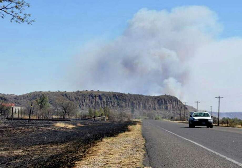 WIth mile rising from a wildfire in the background, a state trooper drives along a road in Fort Davis, Texas, Sunday, April 10, 2011. A fast-moving wildfire had spread to more than 60,000 acres in Presidio County and Jeff Davis County, where it destroyed about 20 homes in Fort Davis. Photo: AP